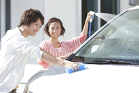 家の前で洗車をする夫婦