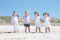 砂浜で手をつなぐ子供4人