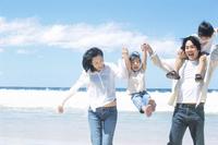 砂浜で遊ぶ家族4人