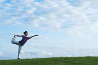 芝生の上でヨガをする女性