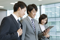 タブレットPCを見るビジネス男女3人