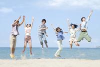 砂浜でジャンプをする6人の男女