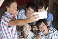 飲食店で写真を撮る男女6人