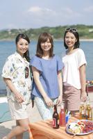 浜辺でバーベキューをする女性3人