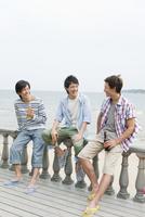 手すりに座って話す3人の男性