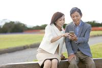 携帯電話を見ている中高年夫婦