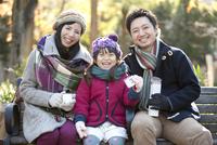 公園のベンチに座る家族3人