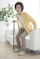 ソファーから立ち上がる中高年女性
