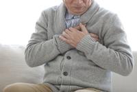 胸を押さえる中高年男性