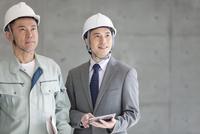 建設現場を見る男性2人
