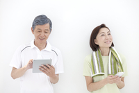 タブレットPCとスマートフォンを操作する中高年夫婦