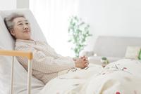 介護ベッドに横になるシニア女性