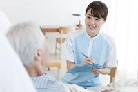 カルテを書く女性介護士とシニア男性 07800048413| 写真素材・ストックフォト・画像・イラスト素材|アマナイメージズ