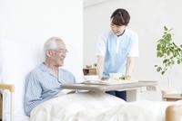食事を運ぶ女性介護士とシニア男性