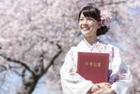 卒業証書を持つ袴姿の女子大生