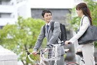 自転車を押すビジネスマンとビジネスウーマン