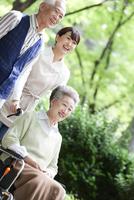 介護士と車椅子に乗る老夫婦