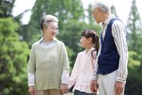 手をつなぐ老夫婦と孫
