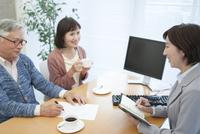 商談中のビジネスウーマンとシニア夫婦