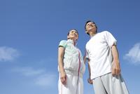 青空とスポーツウェアを着たシニア夫婦