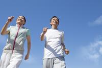 青空とジョギングをするシニア夫婦