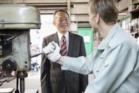 機械を操作する外国人作業者とビジネスマン