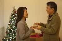 クリスマスプレゼントを渡すシニア夫婦