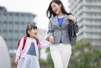 手をつないで歩く女の子と母親