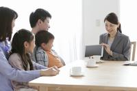 ビジネスウーマンの説明を聞く家族4人