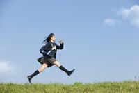 土手を走る女子校生 07800053417  写真素材・ストックフォト・画像・イラスト素材 アマナイメージズ