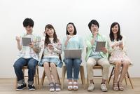 電子機器を操作する若者5人