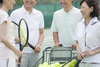 テニスコートで話す男女4人