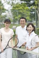 テニスコートに立つ男女3人