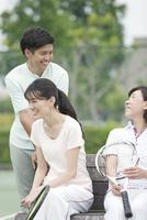 テニスコートで休憩する男女3人