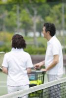 テニスをする中高年カップルの後姿
