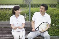 テニスコートで休憩する中高年カップル