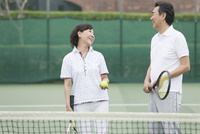 テニスをする中高年カップル