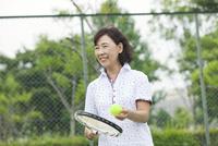 テニスをする中高年女性