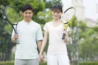 テニスコートに立つカップル