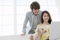 ノートパソコンを見るカップルと犬