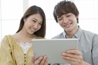 タブレットPCを見ているカップル