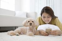 スマートフォンを操作する女性と犬 07800054369| 写真素材・ストックフォト・画像・イラスト素材|アマナイメージズ