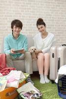 旅行の準備をするカップルと犬