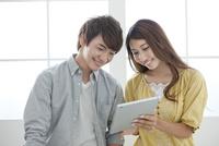 タブレットPCを操作するカップル