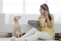 音楽を聴く女性と犬 07800054402| 写真素材・ストックフォト・画像・イラスト素材|アマナイメージズ