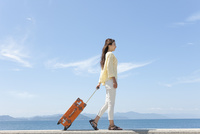 スーツケースを引いて歩く女性