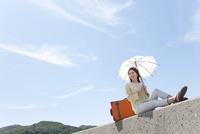 堤防に座る女性 07800054593  写真素材・ストックフォト・画像・イラスト素材 アマナイメージズ
