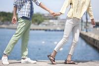 海岸で手をつなぐカップル