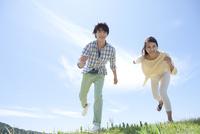 芝生を走る男女 07800054606  写真素材・ストックフォト・画像・イラスト素材 アマナイメージズ
