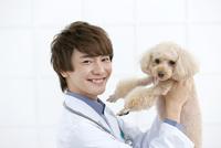 犬を抱き上げる獣医 07800054647| 写真素材・ストックフォト・画像・イラスト素材|アマナイメージズ